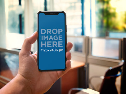 iPhone X Mockup Being Held Against an Office a17678