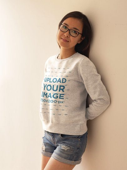 Cute Girl with Glasses Wearing a Crewneck Sweatshirt Template While Lying Against a White Wall a17609