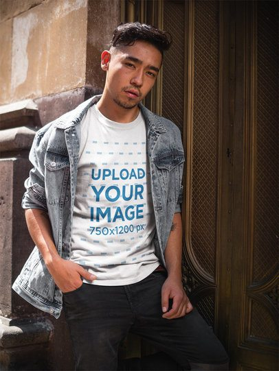 Asian Dude Wearing a T-Shirt Mockup and a Denim Jacket While Against a Golden Door a17796