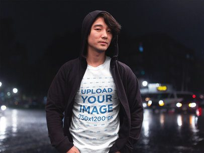 Asian Man Wearing a T-Shirt Mockup While on the Street at Night a17836
