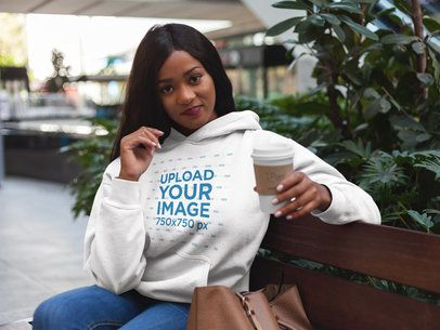 Mockup of a Woman Having a Coffee While Wearing a Pullover Hoodie 17746
