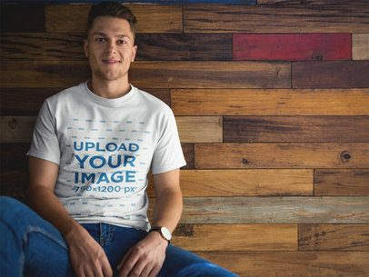 Man Wearing a Tshirt Mockup while Sitting Against a Wooden Wall a17849