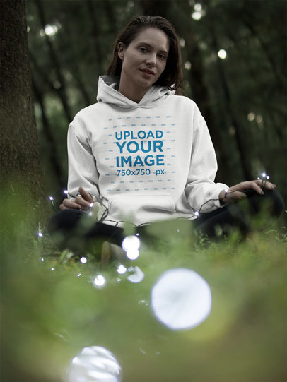 Blonde Woman Wearing a Pullover Hoodie Mockup in the Woods While Holding White Lights a17914