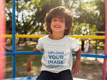 Happy Small Boy Wearing a T-Shirt Mockup While at the Park a17871