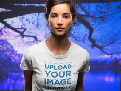 Front Shot of a Beautiful Woman Wearing a T-Shirt Mockup Against a Purple Lake Background a18590