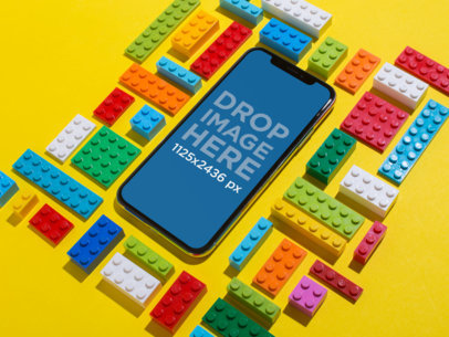Black iPhone X Mockup Lying on a Yellow Surface Surrounded by Blocks Toys a19121
