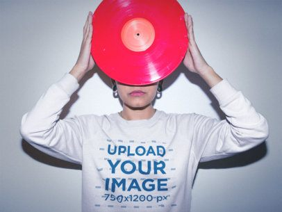 Woman Wearing a Crewneck Sweatshirt Mockup while Holding a Vinyl Against her Face a18821
