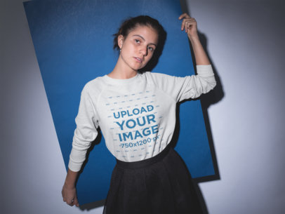 Girl Wearing a Crewneck Sweater Mockup while Holding a Blue Poster Board Against her Back a18504