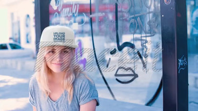 Young Skater Girl Wearing a Snapback Hat Video while Sitting in a Bus Stop with Graffiti a14138