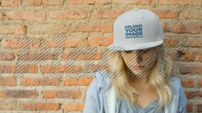 Young Woman Wearing a Snapback Hat Video While Standing Against a Bricks Wall a14139