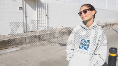 Woman Wearing Hoodie Video Mockup and Sunglasses Sitting on Bumper Industrial Street a13095