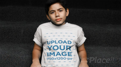 Young Boy Sitting on Some Stairs Wearing a Kid's T-Shirt Video Mockup a12770
