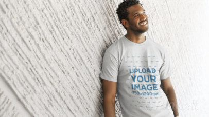 Video of a T-Shirt Being Worn by a Young Handsome Black Man Smiling and Chilling Against a Textured Wall a12777