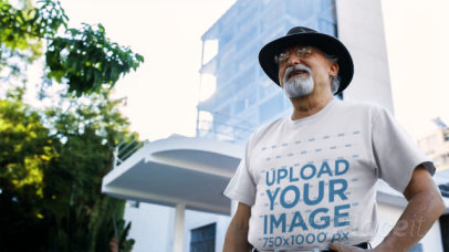 Senior Man Wearing a Round Neck Tshirt Video and a Hat while in the City a12783