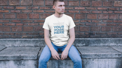 Trendy Guy Sitting in a Downtown Street Wearing a Simple Round Neck Tee Video Mockup a12231