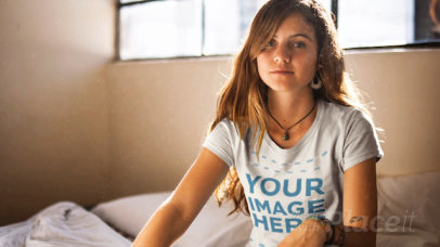 Pretty Young Girl Sitting in Bed Wearing a Round Neck T-Shirt Cinemagraph Mockup a13318