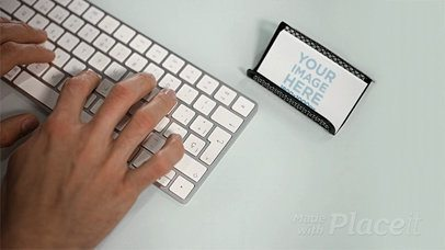 Business Card Lying in a Holder on a Desktop While a Man is Typing a Keyboard in Stop Motion a13727