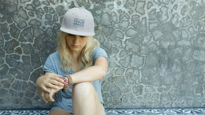 Blonde Girl Wearing a Snapback Hat Video While Sitting Down Against a Wall a14141