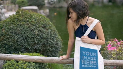 Mockup Video Of A Pretty Girl Holding A Tote Bag While Near A Pond a13877b