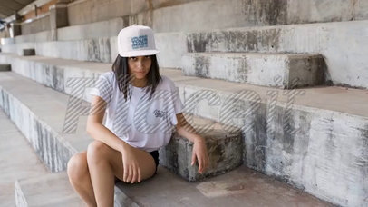 Young Girl Wearing a Snapback Hat Video Making Faces Sitting on Concrete Stairways a14203