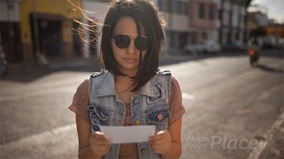 Young Trendy Girl Showing You a Flyer in Stop Motion While on the Street a13739