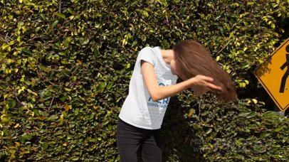 Trendy Girl Flipping her Hair in the Street Wearing a Round Neck T-Shirt Stop Motion a13161