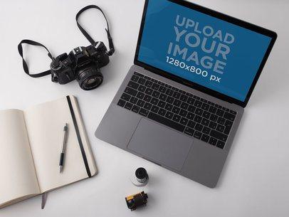 MacBook Pro Mockup Lying on a White Desk Near an Analog Camera a19516