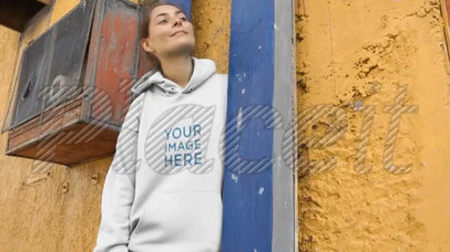 Young Girl Lying Against a Blue Metal Structure And Yellow Wall Wearing a Hoodie Video a13099