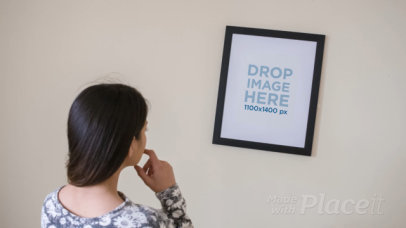 Young Girl Adjusting a Framed Art Print on her White Wall Video a14361