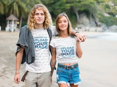 Surfer Couple Wearing Tshirts Mockup Walking on the Beach a18800
