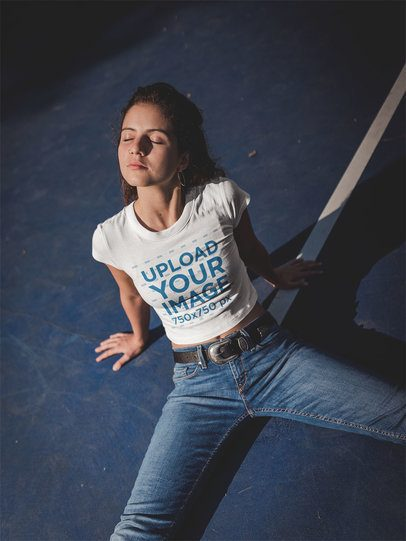 Girl Wearing a Crop Top Tshirt Mockup Sitting at a Blue Court at Night a19328