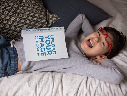 Hispanic Kid Laughing with a Book Mockup on Bed a19152