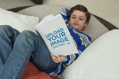 Little Boy Reading a Book Mockup Lying on a Pillows a19207