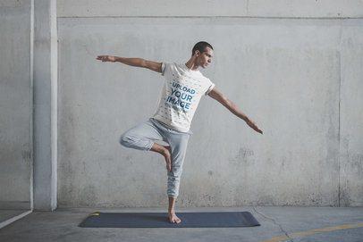 Man Balancing Wearing a T-Shirt Mockup at the Yoga Class a20029