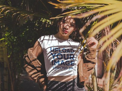 Girl Wearing a T-Shirt Mockup Under Palms and a Brown Jacket a19315