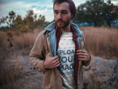 Sad Man Walking Outdoors Wearing a T-Shirt Mockup a19029