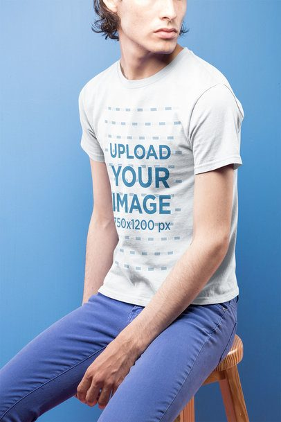 Closeup of a Dude Wearing a Short Sleeved T-Shirt Mockup Against a Blue Background a19666
