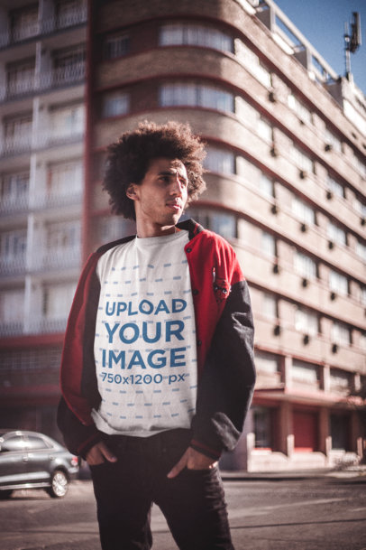 T-Shirt Mockup of a Man with Afro Hairstyle Standing Against a Building on the Street a18909