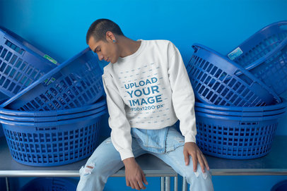 Man Wearing a Crewneck Sweatshirt Template Sitting Between Baskets at the Laundry a19704