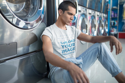 Man Wearing a T-Shirt Mockup and Jeans at a Laundry a19702