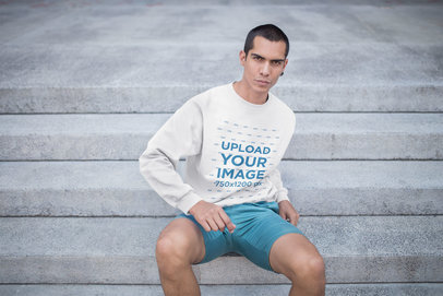 Serious Man Wearing a Crewneck Sweatshirt Mockup Sitting on Concrete Stairs a19708