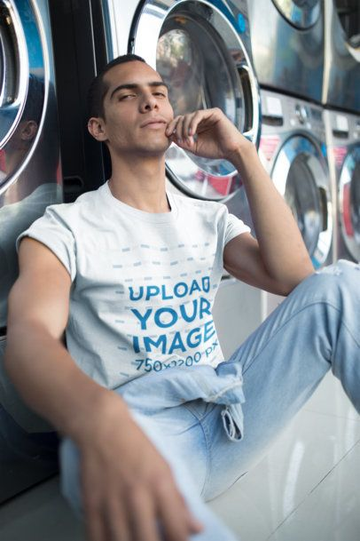 Man Wearing a T-Shirt Mockup Resting at a Laundry a19703