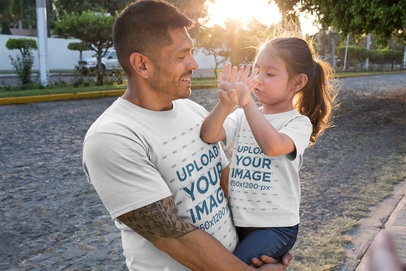 Dad and Daughter T-Shirt Mockup Featuring a Man Raising his Daughter on the Street a19859