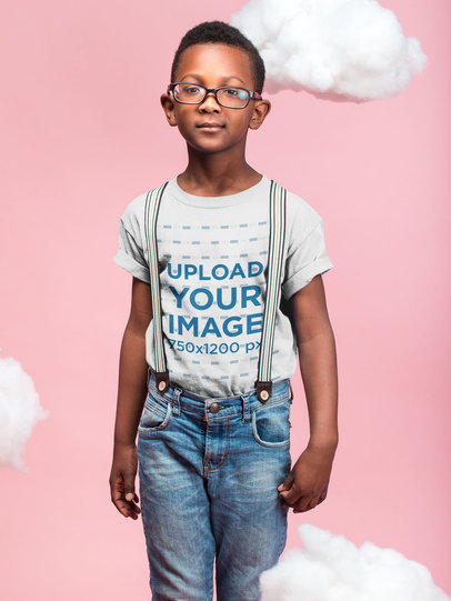 Black Boy with Glasses Wearing a T-Shirt Mockup Against a Pink Background with Clouds a19726