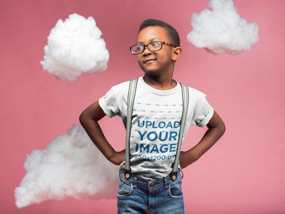 Black Kid Wearing a T-Shirt Mockup and Glasses while Standing in a Pink Room with Clouds a19727