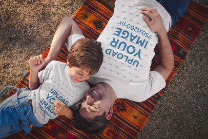Dad and Boy Wearing T-Shirts Mockup Lying Down at the Park a20190