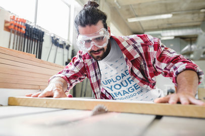 Carpenter Wearing a T-Shirt Mockup while Cutting Wood a20168