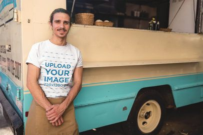 Man Wearing a Round Neck Tee Mockup Standing Against his Foodtruck a20306