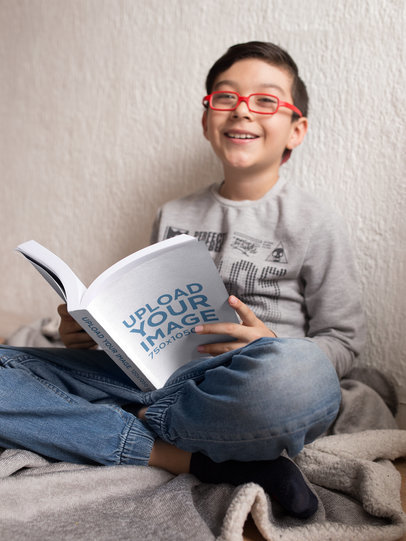 Mockup of a Happy Boy with Red Glasses Reading a Book in His Room a19149