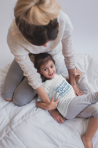 Little Girl Wearing a Tshirt Mockup while Playing with her Mom on the Bed a20284